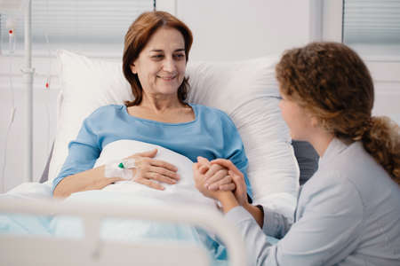 Smiling elderly woman and caring daughter holding her hand in the hospital