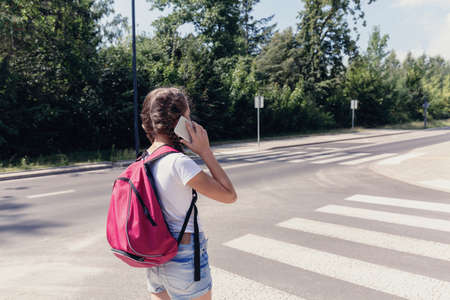 Girl with backpack using smartphone while walking through pedestrian crossing
