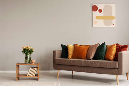 Roses in glass vase on wooden shelf with books next to comfortable sofa with orange, yellow, beige and emerald green pillows Stock Photo - 121161938