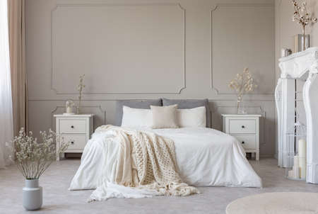 King size bed with white sheets and blanket between two wooden bedside tables flowers in vases