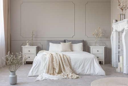 Lit king size avec draps blancs et couverture entre deux tables de chevet en bois fleurs dans des vases