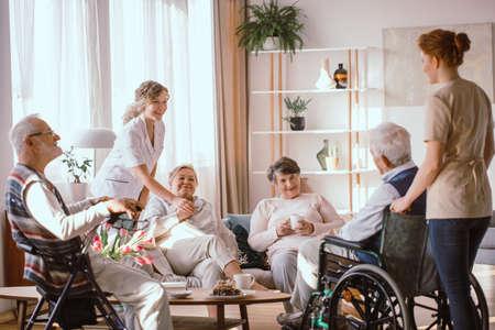 Gehandicapte grootouders brengen tijd door in de gemeenschappelijke ruimte met hun verzorgers