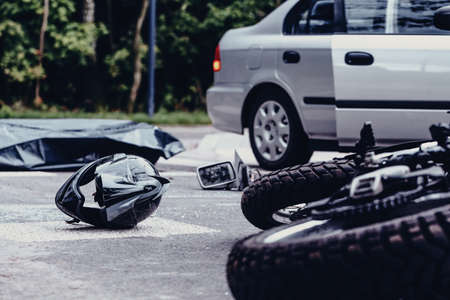Motorcycle helmet on the street after terrible car crash, black bag with corpse and car with open door next to it Reklamní fotografie