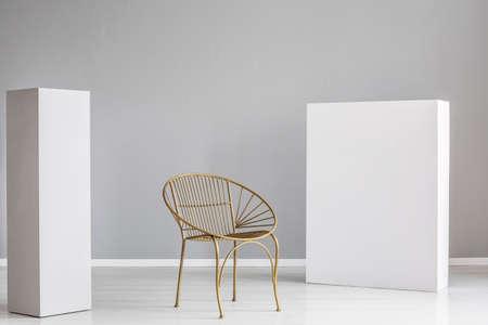 Modischer goldener Stuhl zwischen zwei weißen Holzblöcken Standard-Bild