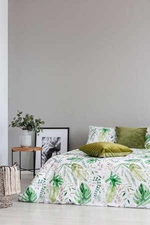 Copie el espacio en la pared gris vacía del acogedor dormitorio con patrón de hojas en la ropa de cama y almohadas de color verde oliva