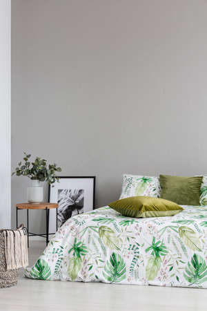 Copy space on the empty grey wall of cozy bedroom with leaf pattern on the bedding and olive green pillows