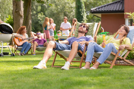 Smiling woman and man relaxing on sunbeds during grill party in the garden