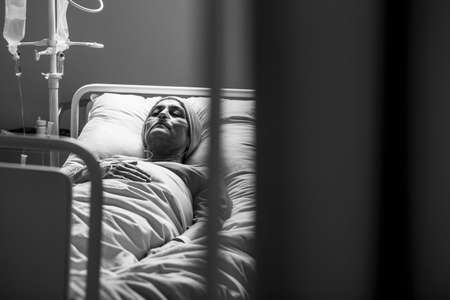 Black and white photo of Weak woman with cancer dying alone in hospital bed
