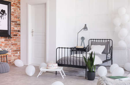Birthday celebration in trendy industrial bedroom with brick wall and metal bed with grey bedding