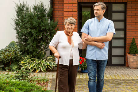 Happy elderly woman with walking stick and friendly caregiver in front of house