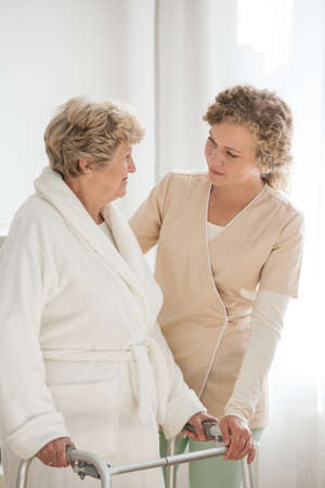 Senior woman in a bathrobe with a walker supported by a nurse