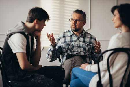 Psychologist talking to depressed teenager and his mum during therapy session