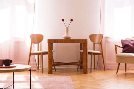 Wooden chairs at table with flowers in bright living room interior with armchair. Real photo