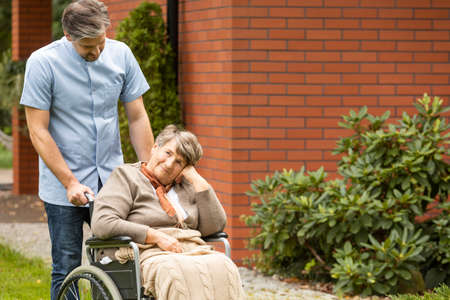 Male nurse supporting disabled senior woman in the wheelchair