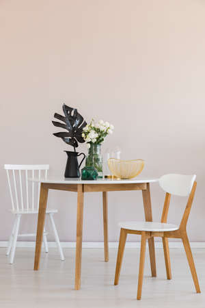 Stylish dining room with round table and elegant chairs, copy space on the empty wall