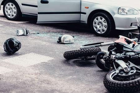 Helm, Spiegel und eine Autolampe zwischen Auto und Motorrad nach schrecklichem Verkehrsunfall Standard-Bild