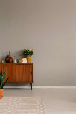 Vases, pile of books and bouquet of roses on vintage cabinet, copy space on empty grey wall