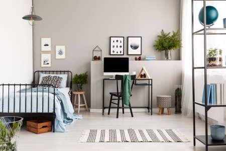 Arbeitsplatz mit industriellem Schreibtisch mit Computer im stilvollen Schlafzimmer des Teenagers mit Postern an leerer grauer Wand und einem einzigen schwarzen Metallbett in der Ecke Standard-Bild