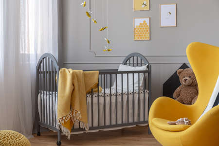 Yellow egg chair and, brown teddy bear and grey wooden crib with blanket in classy baby bedroom