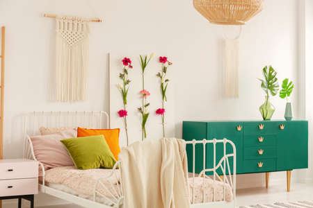 White handmade macrame above single metal bed with colorful pillows and doted bedding in fashionable boho bedroom interior with green cabinet and floral board Stock Photo