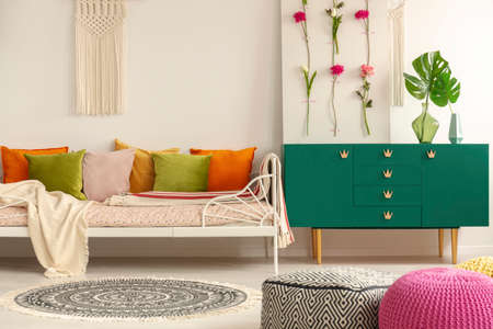 Handmade flower board on green wooden cabinet with leaf in glass vase next to comfortable bed with olive green, pastel pink, yellow and orange pillows