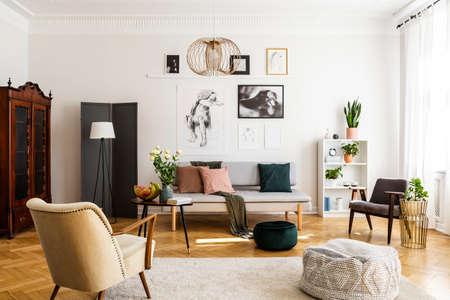 Stylish beige armchair and pouf on the cozy carpet in classy living room interior with grey settee and vintage furniture Stockfoto