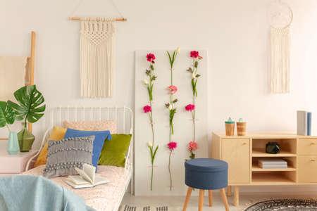 Witte handgemaakte macramé boven een metalen eenpersoonsbed met kleurrijke kussens en gestippeld beddengoed in een trendy boho slaapkamerinterieur