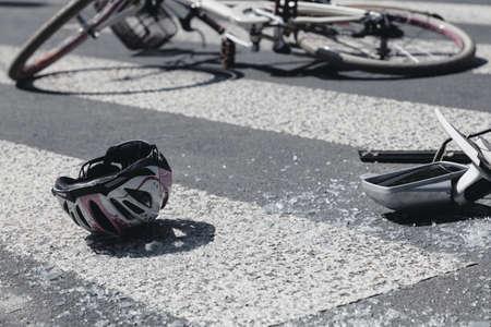 Kids helmet and broken cars mirror next to broken bicycle on pedestrian crossing Stock Photo