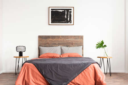 White bedroom with wooden headboard and coral and grey bedsheets Stock Photo