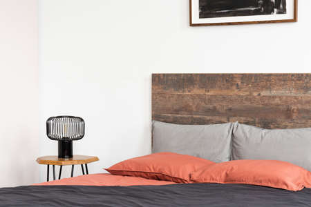 Bed with wooden headboard, coral sheets and black industrial lamp Stock Photo