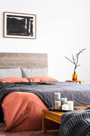 Verticaal schot van houten bed met linnen beddengoed, kunstwerken en oranje vaas