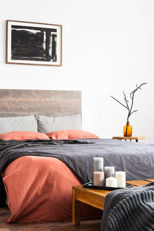 Vertical shot of wooden bed with linen bedclothes, artwork and orange vase