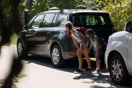 Bruder und Schwester halten sich an den Händen und stehen zwischen Autos, die versuchen, über die Straße zu laufen Standard-Bild