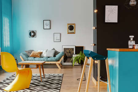 Open space loft interior with blue curtains, lounge with cushions, many posters and black wall by the home bar in real photo Zdjęcie Seryjne