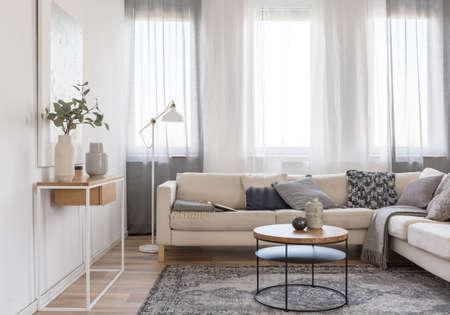 Mesa de centro redonda delante del sofá beige con almohadas en el interior luminoso de la sala de estar con mesa de consola con flores en florero Foto de archivo