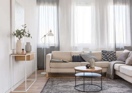 Round coffee table in front of beige sofa with pillows in bright living room interior with console table with flowers in vase Stockfoto