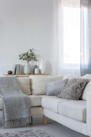 Vista vertical del sofá de la esquina con almohadas y mantas, copie el espacio en la pared blanca vacía