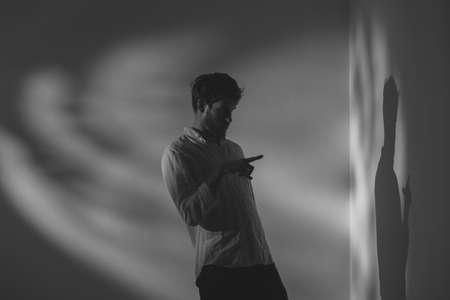 Homme malade atteint de schizophrénie parlant avec sa propre ombre dans une pièce sombre Banque d'images
