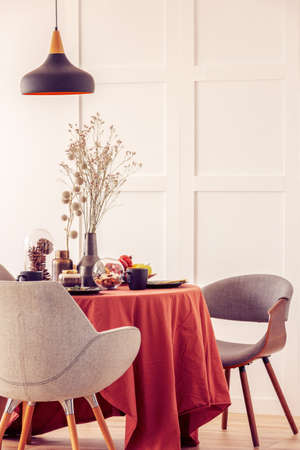 Stylish grey chairs at dining table covered with long tablecloth 스톡 콘텐츠