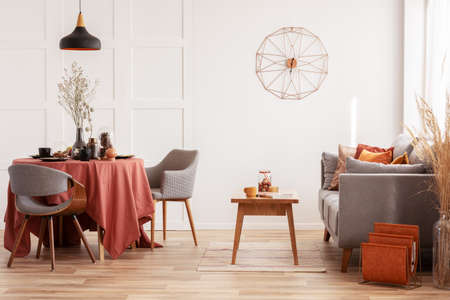 Open eet- en woonkamer met grijze Scandinavische bank en tafel met stoelen with