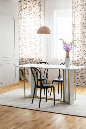 Sheer curtains with pattern on the windows of a classy dining room interior with a pink pendant light and a marble table