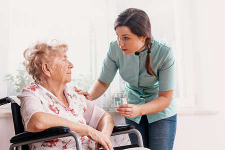 Senior grandmother on wheelchair, supporting nurse giving her glass of water 스톡 콘텐츠