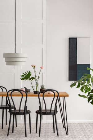 White lamp above wooden table with black chairs