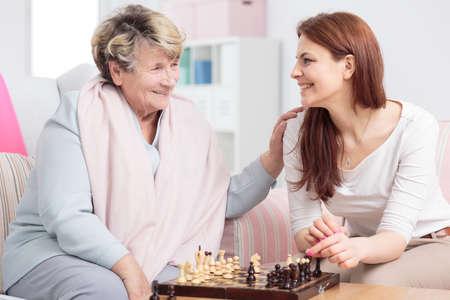 Glückliche Enkelin, die mit ihrer Großmutter im Seniorenzentrum Schach spielt