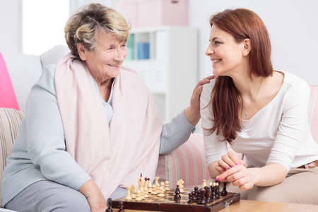 Happy granddaughter playing chess with her grandmother in senior care center