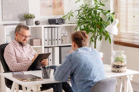 Gestionnaire de compte principal et jeune homme lors d'un entretien d'embauche dans une petite entreprise