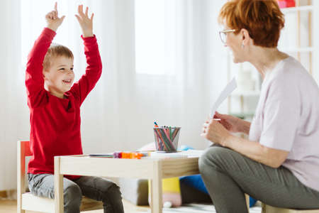 Cute little boy with ADHD during session with professional therapist Standard-Bild