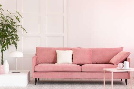 Pastelroze en witte vazen en koffiemokken op kleine tafel in roze woonkamerinterieur met comfortabele bank