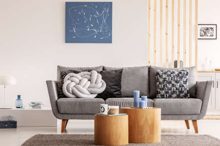 Blue abstract painting on white wall of contemporary living room interior with grey settee with pillows Stock fotó