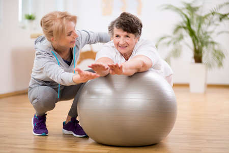 Disabled senior woman exercising on the ball with physiotherapist